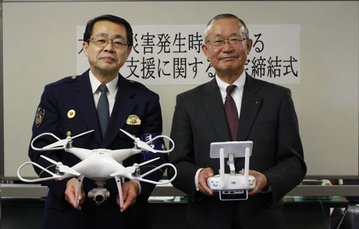 ドローンを手にする神奈川警察署の廣瀬署長(左)と、仙頭社長(右)